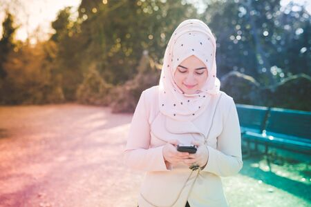 femmes muslim: belle jeune femme musulmane dans le parc au printemps en utilisant smartphone connect� sans fil en ligne Banque d'images