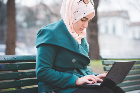 ノートブックを使用して春の公園で若い美しいイスラム教徒女性接続作業のオンライン ビジネス