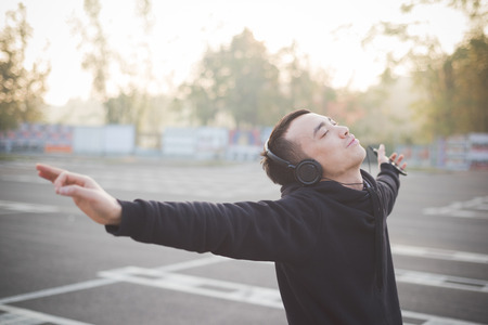 asian style: young crazy funny asian man in town outdoor lifestyle listening music with headphones