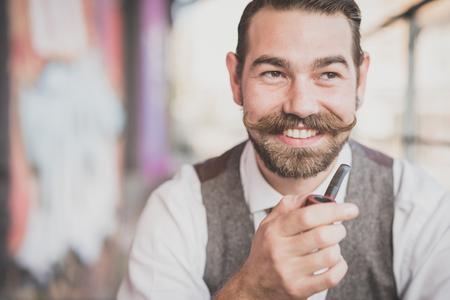 bigote: inconformista bigote pipa que fuma del hombre grande y guapo en la ciudad Foto de archivo