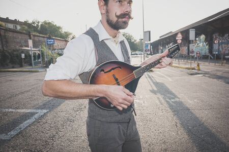 mandolin: handsome big moustache hipster man playing mandolin in the city