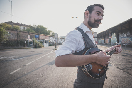 mandolino: bello grande uomo baffi hipster, giocando mandolino in citt� Archivio Fotografico
