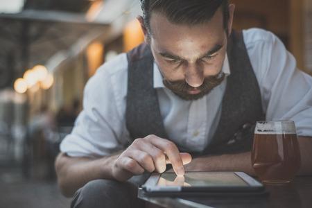 술집에 앉아 태블릿을 사용하여 잘 생긴 큰 콧수염 힙 스터 남자 스톡 콘텐츠