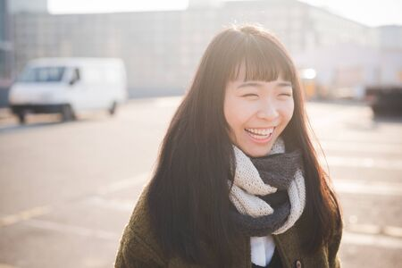 city living: young beautiful asian hipster woman in the city - living town during sunset in backlit - smiling happy