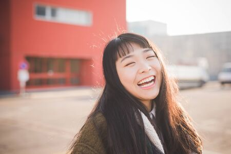 city living: young beautiful asian hipster woman in the city - living town during sunset in backlit smiling happy