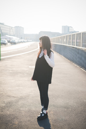 city living: young beautiful asian hipster woman in the city - living town during sunset in backlit
