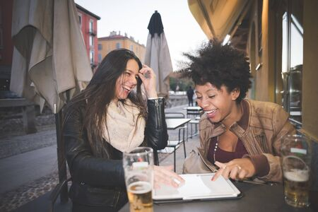 woman black: two multiethnic beautiful young woman black and caucasian using tablet in town
