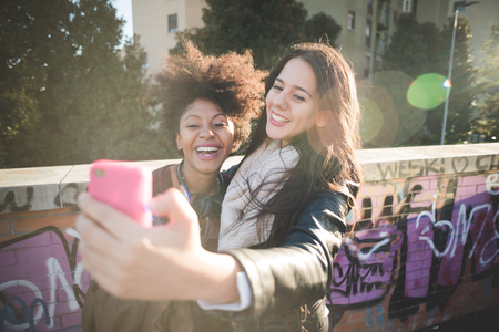 black and black: two multiethnic beautiful young woman black and caucasian having fun taking selfie in town