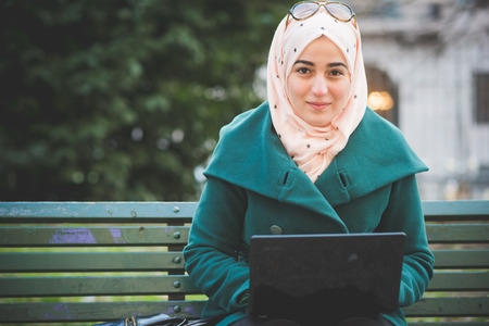 young beautiful muslim woman at the park in spring using notebook connected online working business