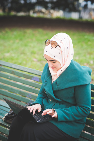arab spring: young beautiful muslim woman at the park in spring using notebook connected online working business