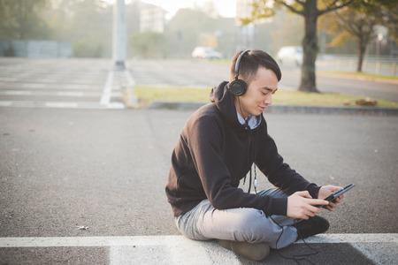 クレイジー面白いアジアの若者町アウトドア ライフ スタイルがヘッドフォンとタブレットで音楽を聴く 写真素材