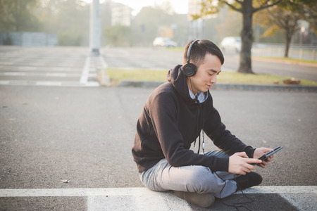listening device: young crazy funny asian man in town outdoor lifestyle listening music with headphones and tablet