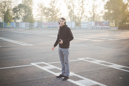 young crazy funny asian man in town outdoor lifestyle listening music with headphones photo