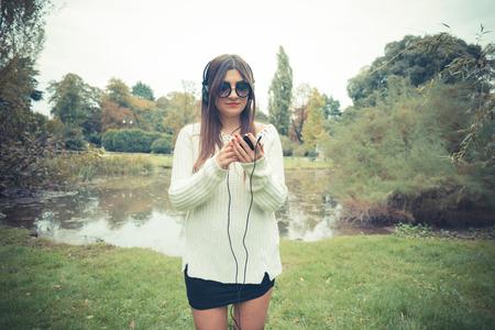 audifonos: jóvenes hermosas auriculares de música chica escucha mujer morena al aire libre Foto de archivo