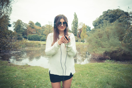 listening device: young beautiful brunette woman girl listening music headphones outdoor