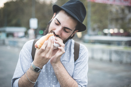 young handsome hipster gay modern man eating hot dog in town