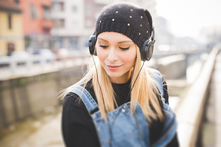 listening to people: young beautiful blonde straight hair woman in the city with headphones listening to music