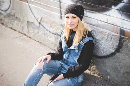 sitting on the ground: young beautiful blonde straight hair woman in the city using smartphone connected online sitting in the ground