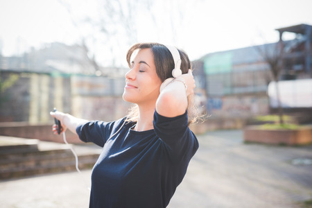 headphones: young pretty woman in town listening music with headphones