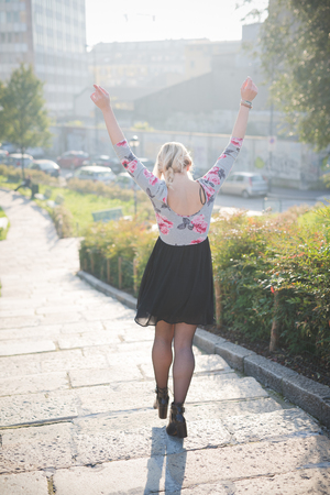 happiness or success: Young and beautiful caucasian blonde girl walking through the city with raised arms, at dusk wearing a floral dress with a black skirt - freedom, happiness, success concept Stock Photo