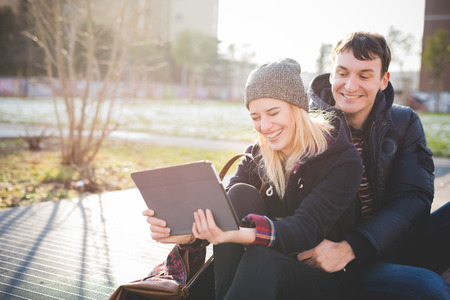 sitted: A couple of young lovers, sitted on a sidewalk, having fun while using a tablet connected on internet. city. She is wearing a brown hat, a black winter coat and black jeans. He is wearing blue jeans and a blue jacket.