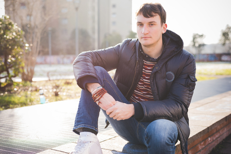 sitted: A young handsome man sitted on a sidewalk, when in the city is getting dusk, wearing blue jeans and a blue jacket. Stock Photo