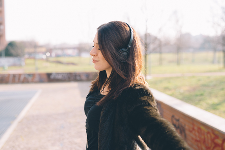happyness: Young beautiful brunette caucasian girl listening to the music with headphones in a city park, with arms wide ope,- music, relax, serenity, success, happyness  concept
