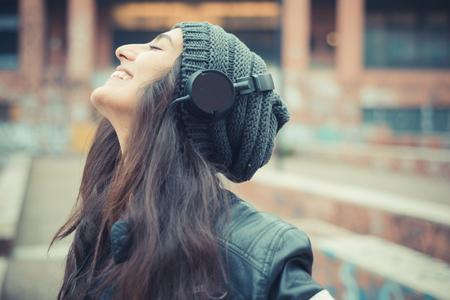 personas escuchando: joven y bella mujer morena escuchar música con auriculares en la ciudad Foto de archivo