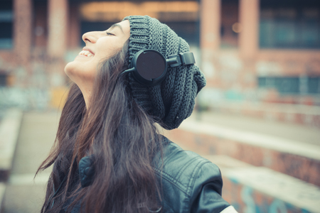 headphones: young beautiful brunette woman listening music with headphones in the city