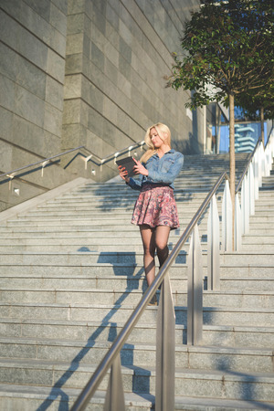 Stock Photo   Young Beautiful Blonde Caucasian Girl Using A Tablet  Connected Online On A Staircase Outside In The City Wearing Jeans Shirt And  Floral Skirt ...
