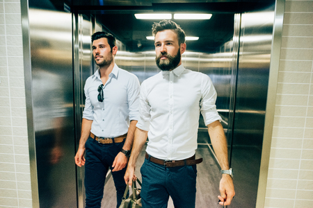 Two young handsome black and blonde hair modern businessman exiting from a elevator, one holding a bag, both overlooking right - business, working, successful concept Standard-Bild