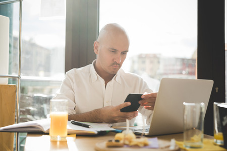 the thoughtful: Half length of young handsome caucasian bald business man sitting in a bar using a laptop leaning on his knees, looking downward the screen, pensive - working, thoughtful, busy concept Stock Photo