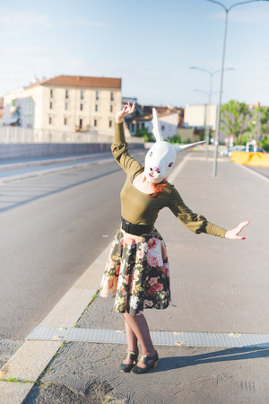dreamlike: young handsome caucasian redhead woman with rabbit mask, dancing in the street of the city, holding a strip of her floral skirt - absurd, strange, dreamlike concept