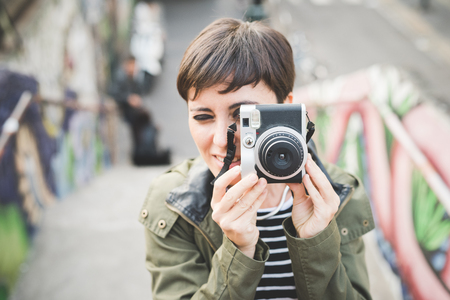 Half length of young handsome caucasian brown straight hair woman taking a photo with vintage camera - artist, creative concept