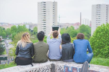 mujer mirando el horizonte: Grupo de amigos multi�tnicas j�venes sentados en una peque�a pared, visto desde atr�s, mirando el horizonte - futuro, prospectivo, el concepto de la amistad