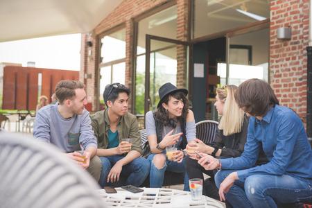 バーで座っている若い民族の友人のグループの概念をリラックス楽しんで - 幸せな時間、友情、お互いに話して、酒を飲む 写真素材