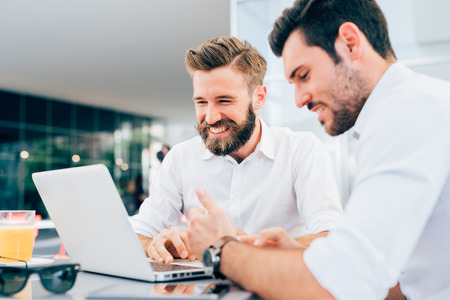 busy beard: Two young bearded caucasian modern business man sitting in a bar, using laptop, looking downward, tapping on keyboard  - business, work, technology concept - focus on blonde hair man Stock Photo