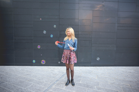 emancipation: Young handsome blonde caucasian girl having fun playing with soap bubble in the city wearing jeans shirt and floral skirt - emancipation, carefreeness, youth concept Stock Photo