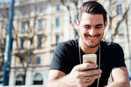 handsome  portrait: Portrait of a young handsome italian boy using a smartphone connected online, looking downward the screen, smiling - technology, social network concept