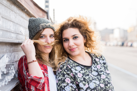 two and a half: Half length of two young curly and straight blonde hair caucasian woman leaning on a wall, one playing with the others hair, use it in shape of mustache - youthful, carefreeness, friendship concept Stock Photo