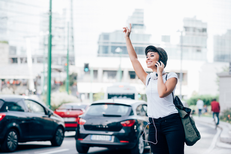 Knee figure of young handsome caucasian brown straight hair woman asking for a taxi raising her arms while talking smartphone, overlooking right, smiling - technology, communication, transport concept