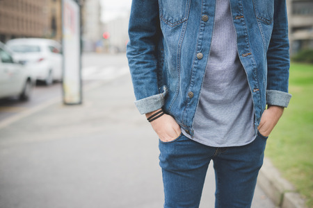 men in jeans: Cropped front view of young handsome alternative dark model man posing in town with hands in pocket - wearing gray shirt, jeans pants and jacket