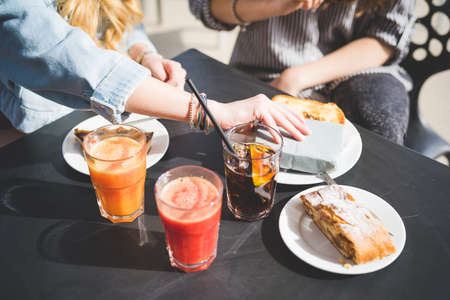 hands  hour: Two young handsome caucasian and eastern women having an happy hour in a bar - close up on hands and food and drinks Stock Photo