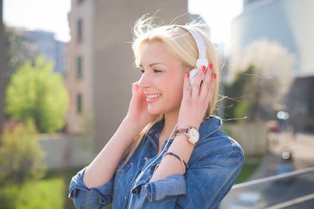 emancipation: Half length of a young beautiful caucasian blonde girl listening to music in the city with headphones overlooking right- relax, youth, emancipation concept