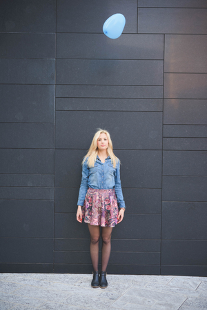 hearted: Young beautiful blonde girl posing leaning on a wall with a hearted balloon flying outdoor in the city looking in camera wearing a jeans shirt and a floral skirt Stock Photo