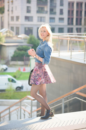 poser: Young beautiful blonde girl posing on a staircase outdoor in the city overlooking on her right wearing a jeans shirt and a  floral skirt - youth, carefreeness, freshness concept