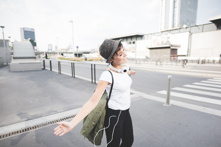 arms wide open: Knee figure of young handsome caucasian brown straight hair woman dancing with arms wide open and headphones around her neck through the street of the city, smiling - feeling free, freedom, dancing concept