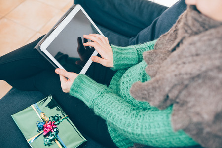 social network: Close up on the hand of young handsome woman tapping on the screen of a tablet sitting on the sofa, gift place on her side- technology, communication, social network concept Stock Photo
