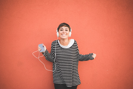 mujeres morenas: Media longitud de la joven y guapo cauc�sico marr�n recta escuchar m�sica con auriculares mujer de pelo apoyado contra una pared, mirando en la c�mara sonriente, sosteniendo tel�fono inteligente - tecnolog�a, concepto de la m�sica Foto de archivo