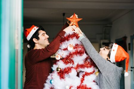 topper: Half length of couple of young handsome caucasian man and woman decorating christmas tree, putting tree topper star - christmas, holiday concept